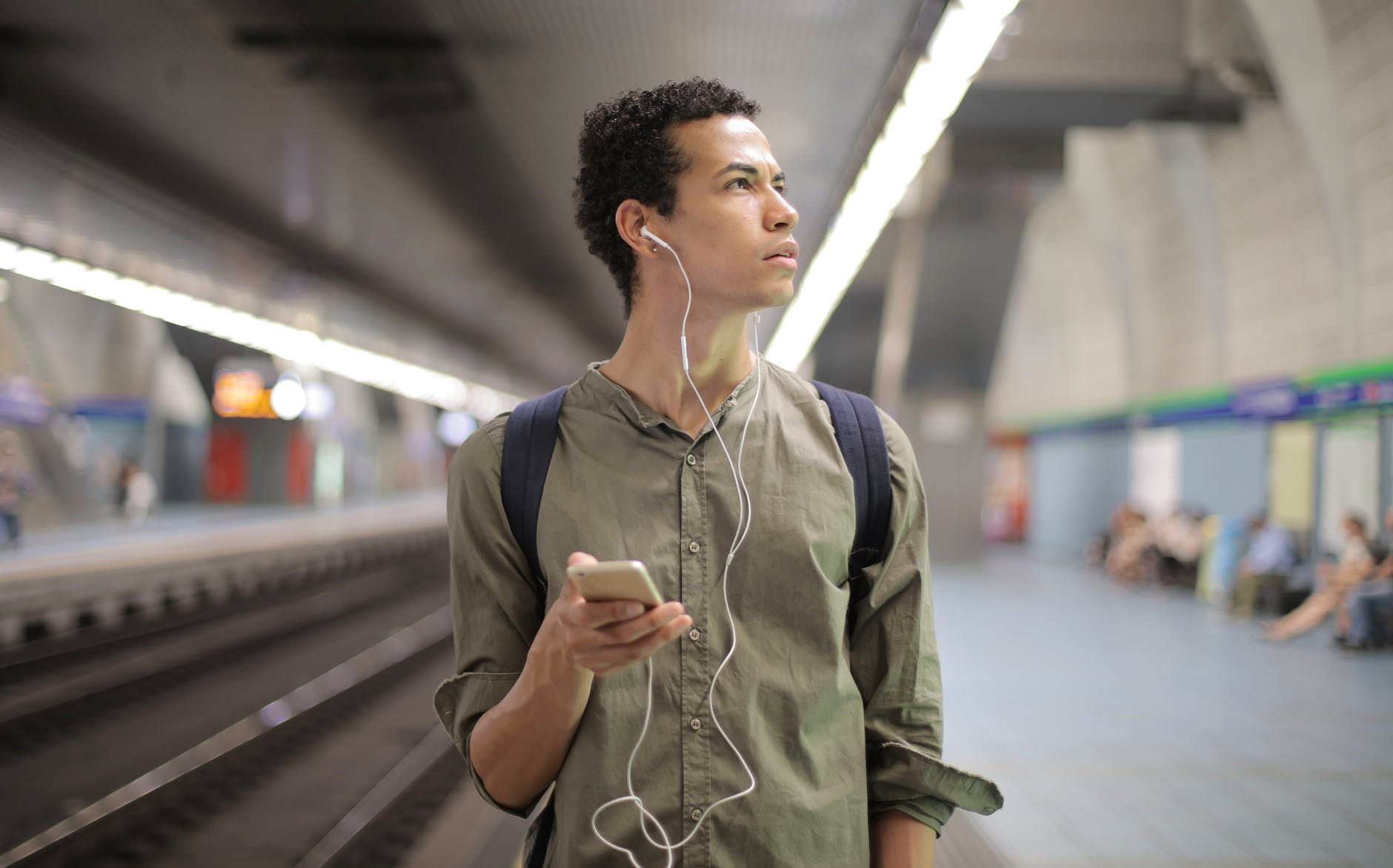 young ethnic man in earbuds listening to music while waiting for transport at contemporary subway station